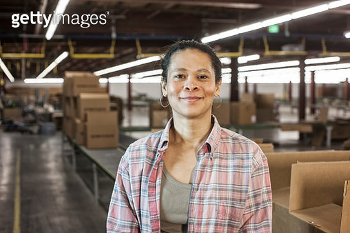 Portrait of an African American female warehouse worker in a large distribution warehouse with products stored in cardboard boxes. - gettyimageskorea