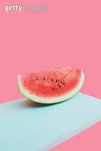 Close-Up Of Watermelon Slice On Cutting Board Against Pink Background - gettyimageskorea