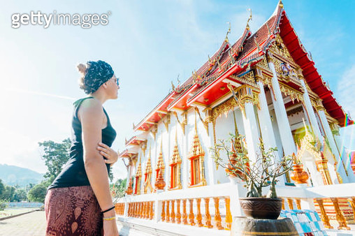 Young woman discovers Thai temple - gettyimageskorea