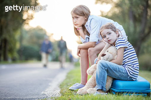 Two girls sitting on suitcase at the roadside - gettyimageskorea