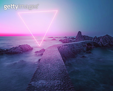 Stunning triangle shape made with neon light performing in the coast with path between rocks during sunrise. - gettyimageskorea