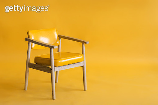 Bright yellow leather and wood armchair is standing in an empty yellow background. Concept of minimalism. - gettyimageskorea
