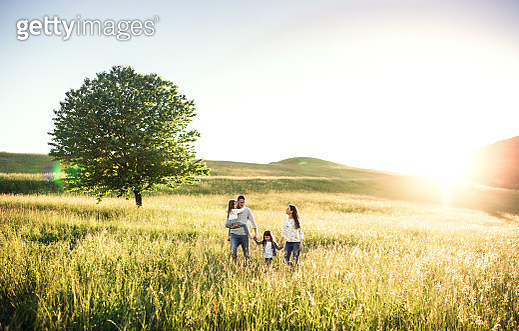 Happy family with two small children walking outside in spring nature at sunset. - gettyimageskorea