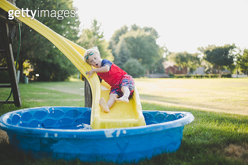 Little boy slides down a yellow play structure slide into a kiddy pool on a warm summer day. - gettyimageskorea