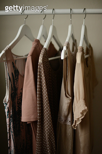 blouses in a similar color shade hanging on a coat hangers on a rack - gettyimageskorea