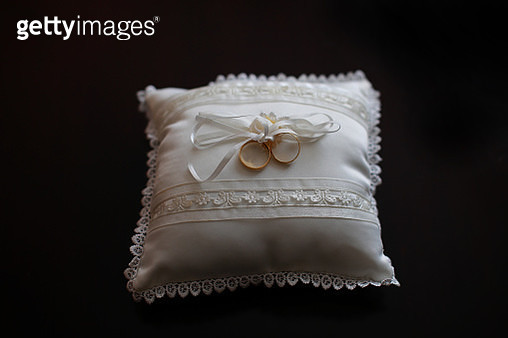 Close-Up Of Wedding Rings On Cushion Against Black Background - gettyimageskorea
