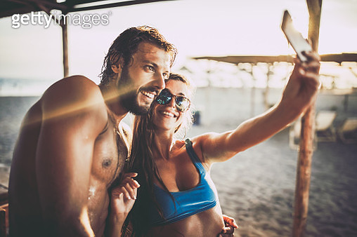 Happy couple taking a selfie with cell phone on the beach. - gettyimageskorea