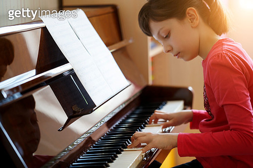 Girl playing the piano - gettyimageskorea