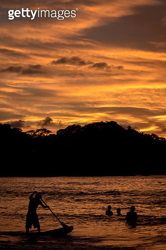 Silhouette Man Paddleboarding On Sea Against Sky During Sunset - gettyimageskorea