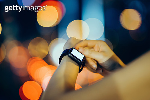 Close up of human hands using smart watch in city at night against multi coloured street lights - gettyimageskorea
