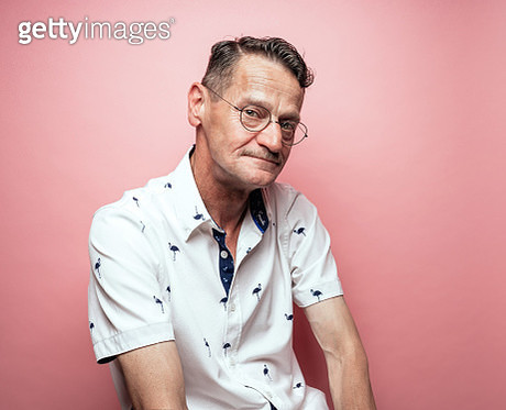Middle-aged man with glasses on pink background - gettyimageskorea