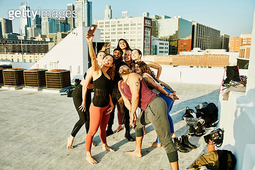 Smiling friends taking group selfie after rooftop yoga class - gettyimageskorea