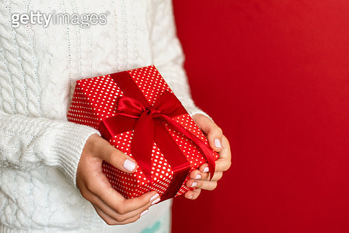 Female hands holding present with red bow on white rustic sparkling background. Festive backdrop for holidays: Birthday, Valentines day, Christmas, New Year. Flat lay. - gettyimageskorea