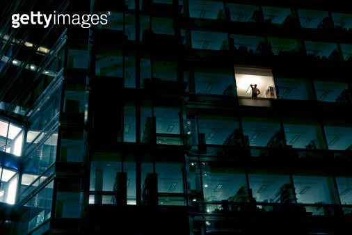 Office building at night, man standing in one illuminated window, low angle view - gettyimageskorea