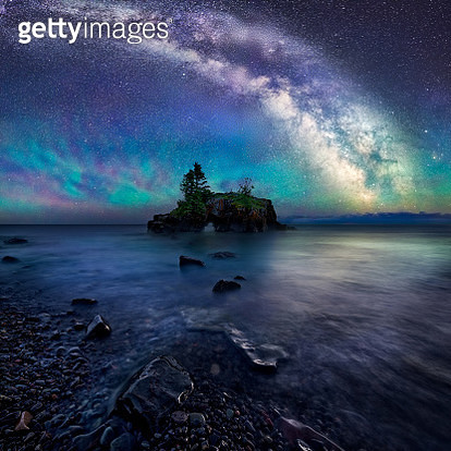 Hollow rock is an iconic coastal formation located on the North West side of Lake Superior. Air glow creates a colorful luminescent atmosphere below the night sky and Milky Way. A long exposure captures the faint stars and creates a smooth watery surface  - gettyimageskorea
