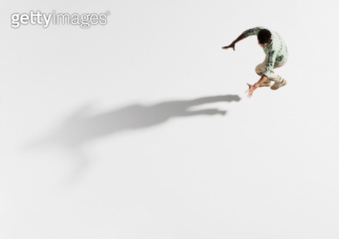 Young man jumping, holding arms out towards shadow, overhead view - gettyimageskorea