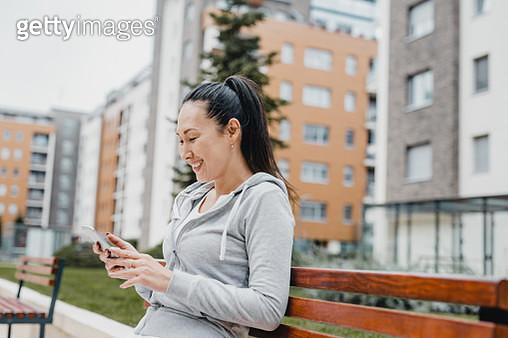 Portrait of Asian woman in sportswear. She wears grey sweatshirt and has headphones on her neck - gettyimageskorea