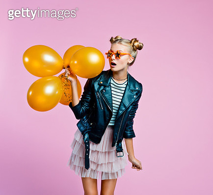 Surprised female teenager wearing black leather jacket, pink tulle skirt and star shaped sunglasses holding bunch of gold balloons. Studio shot on pink background. - gettyimageskorea