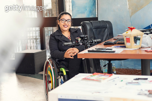 Portrait of a young woman with physical disability working  in the office. - gettyimageskorea