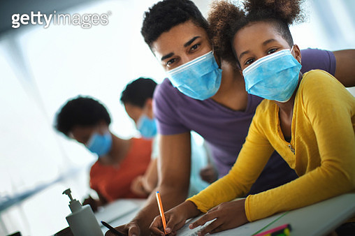 Closeup front view of a mid 30' man helping is daughter with homeschooling during coronavirus quarantine. They are wearing face masks and looking at the camera for a moment. Mother and son are in the background. - gettyimageskorea