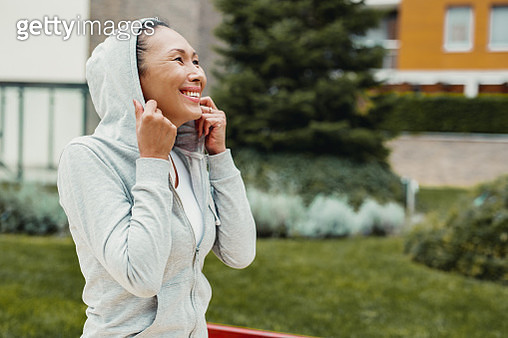 Portrait of Asian woman in sportswear. She has her hoodie on and smiling - gettyimageskorea