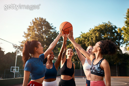 Cropped shot of a diverse group of sportswomen holding a basketball together before playing a game during the day - gettyimageskorea
