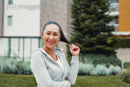 Portrait of Asian woman in sportswear. She wears grey sweatshirt and looking at camera outdoors - gettyimageskorea