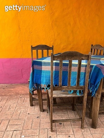 Empty Chairs And Table Against Yellow Wall - gettyimageskorea
