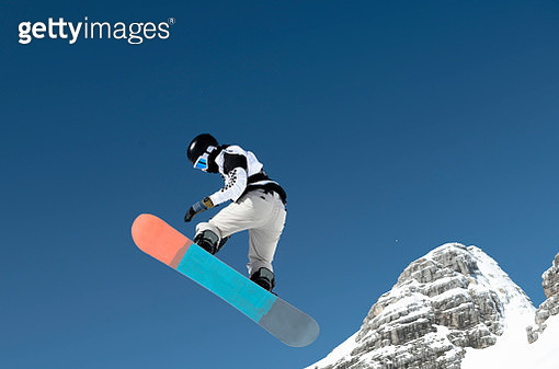 Side View of Young Snowboarder Practicing Big Air - gettyimageskorea