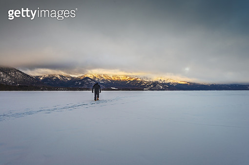 One man trekking towards snow peaks illuminated by rising sun in deep snow field - gettyimageskorea