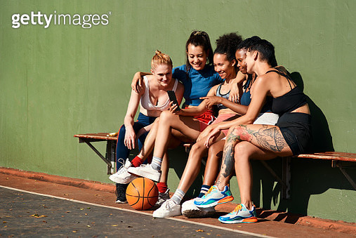 Cropped shot of a diverse group of sportswomen sitting together after playing basketball and looking at a cellphone - gettyimageskorea