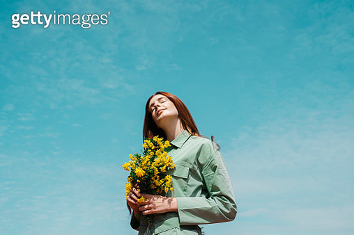Portrait of redheaded young woman with eyes closed standing against sky holding bunch of yellows flowers - gettyimageskorea