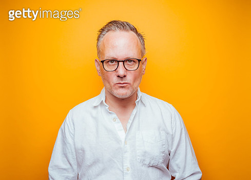 Middle-aged man with glasses on yellow background - gettyimageskorea
