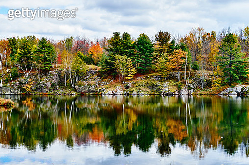 Autumn coloured foliage and clouds in Frontenac Provincial Park reflected in tranquil water - gettyimageskorea