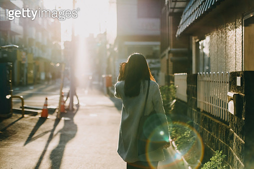 Rear view of woman leaving home to work in the early morning against warm sunlight - gettyimageskorea