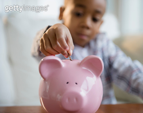 African American boy putting coins in piggy bank - gettyimageskorea