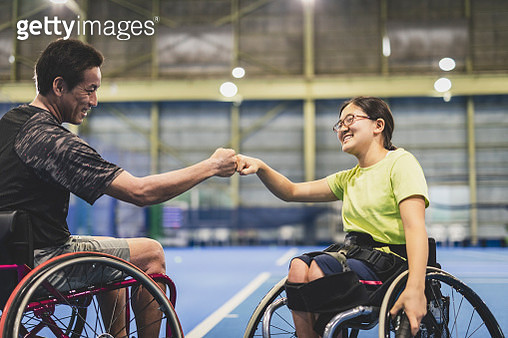 Disabled female athlete doing a fist bump with her coach during playing wheel chair tennis - gettyimageskorea
