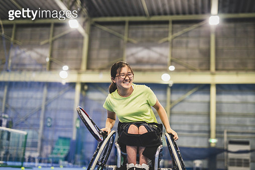 Disabled female athlete playing wheel chair tennis - gettyimageskorea