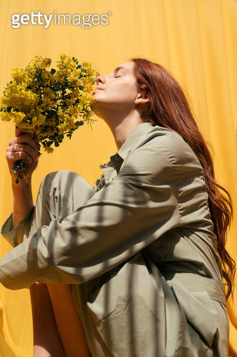 Portrait of redheaded woman with eyes closed holding bunch of yellow flowers against yellow background - gettyimageskorea