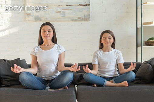Mom with kid daughter doing yoga together - gettyimageskorea