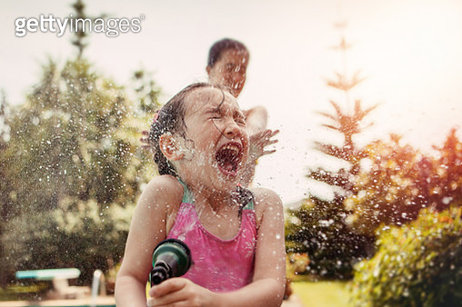 Girl (4-5) in bathing suit sprayed with water hose. - gettyimageskorea
