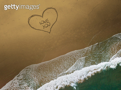 An Aerial shot of a heart with the words 'Love You' written on the sand at the beach - gettyimageskorea