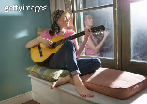 Young woman playing guitar at home. - gettyimageskorea