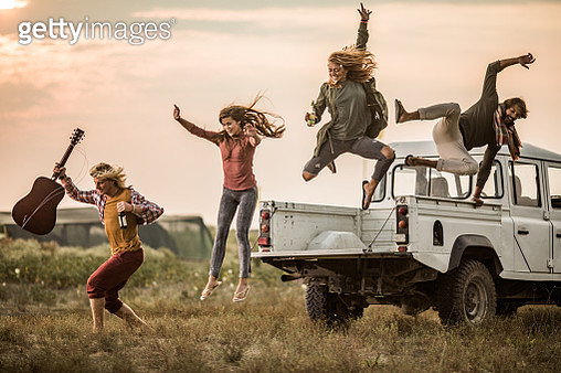 Carefree friends having fun while jumping from the truck at sunset. - gettyimageskorea
