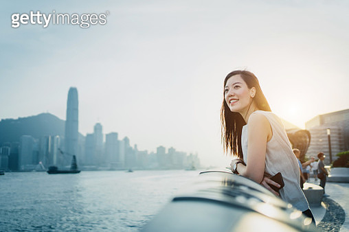 Smiling young Asian woman traveller looking out over promenade of Victoria Harbour enjoying the gentle breeze and the beautiful cityscape at dusk - gettyimageskorea