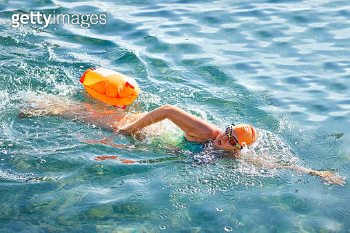 High angle view of mature woman swimming in sea - gettyimageskorea