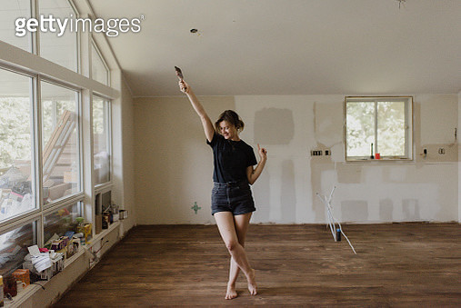 Woman holding paintbrush and dancing in new home - gettyimageskorea