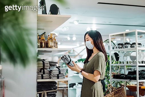 Young Asian woman with protective face mask shopping for household necessities in a homeware store looking at a pack of towels - gettyimageskorea