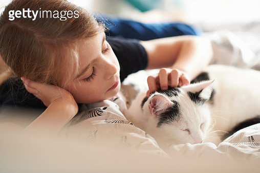 Young girl lying on her bed with her cat - gettyimageskorea