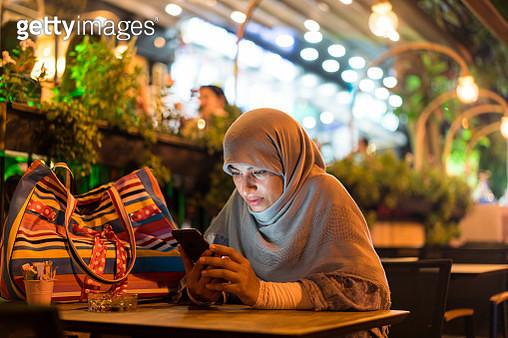 Muslim woman sitting alone using phone - gettyimageskorea